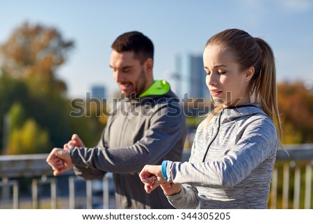 fitness, sport, people, technology and healthy lifestyle concept - smiling couple with heart-rate watch running over city highway bridge - stock photo