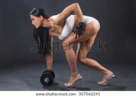 fitness, sport, powerlifting and people concept - sporty woman exercising with dumbbells on dark background - stock photo
