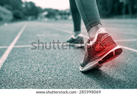 fitness, sport, sports injury, pain and people concept - monochrome close up of woman feet or legs running on track with red spot from back - stock photo