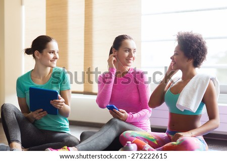 fitness, sport, technology and lifestyle concept - group of happy women with smartphone, earphones and tablet pc computer listening to music in gym - stock photo