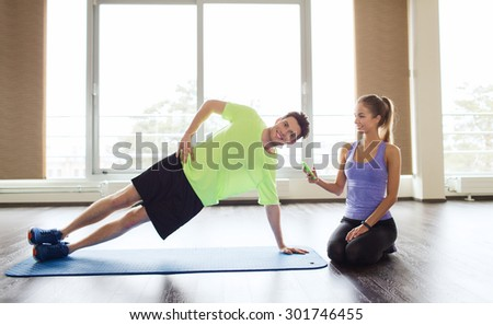 fitness, sport, technology and people concept - man and woman with smartphone doing side plank exercise on mat in gym