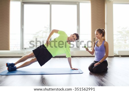 fitness, sport, technology and people concept - man and woman with smartphone doing side plank exercise on mat in gym - stock photo