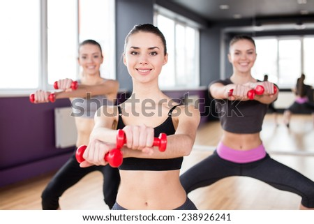 Fitness, sport, training and lifestyle concept. Group of smiling women are stretching in gym with du - stock photo