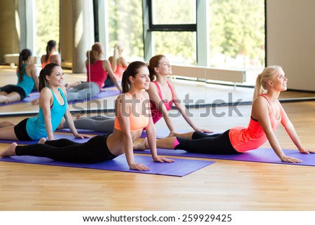 fitness, sport, training and lifestyle concept - group of smiling women stretching in gym