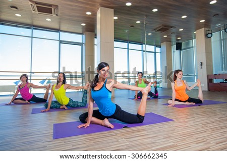 fitness, sport, training and lifestyle concept - group of smiling women stretching in gym. - stock photo