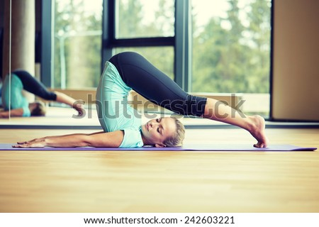 fitness, sport, training and lifestyle concept - smiling woman stretching on mat in gym - stock photo