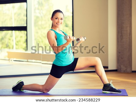 fitness, sport, training and lifestyle concept - smiling woman with dumbbells in gym