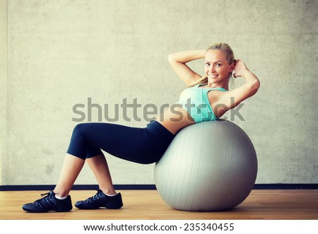 fitness, sport, training and lifestyle concept - smiling woman with exercise ball in gym - stock photo