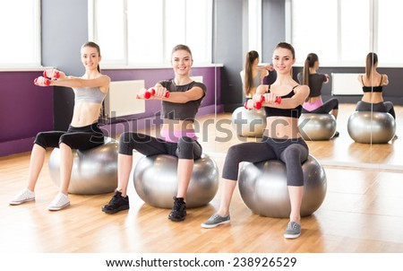 Fitness, sport, training and lifestyle concept - three smiling woman with exercise balls and dumbbells in gym.