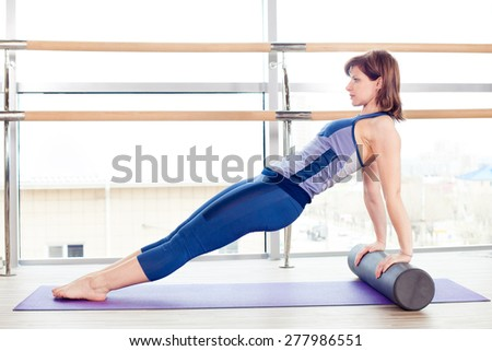 fitness, sport, training and lifestyle concept -  woman doing pilates on the floor with foam roller - stock photo