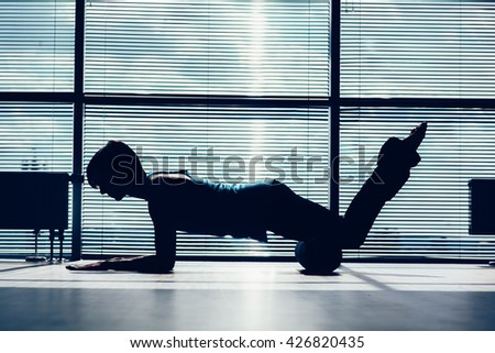 fitness, sport, training and lifestyle concept - woman doing pilates on the floor with foam roller contour of the body against the window - stock photo