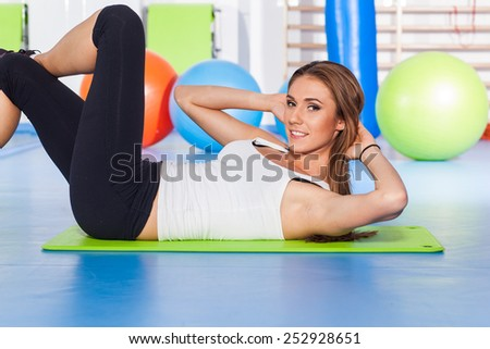 fitness, sport, training and lifestyle concept - woman stretching and doing physical exercises  on mat in gym. - stock photo