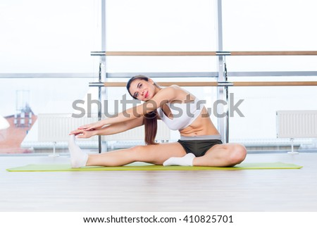 fitness, sport, training and people concept -  Happy young woman stretching before running in gym - stock photo