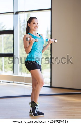 fitness, sport, training and people concept - smiling woman exercising with dumbbells in gym - stock photo