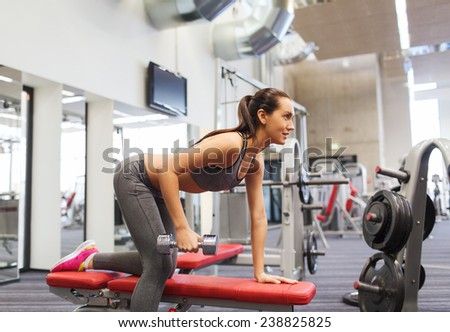 fitness, sport, training and people concept - smiling woman with dumbbell flexing muscles on bench in gym - stock photo
