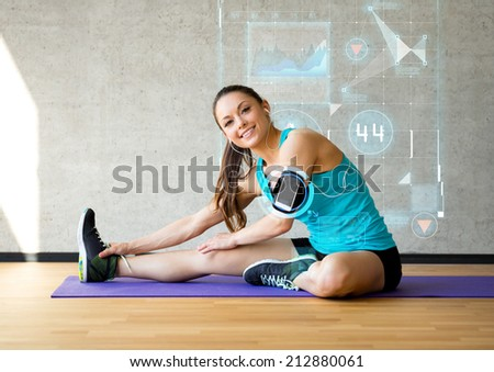fitness, sport, training, future technology and lifestyle concept - smiling woman stretching leg on mat in gym over graph projection - stock photo