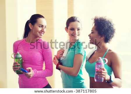 fitness, sport, training, gym and lifestyle concept - group of happy women with bottles of water in gym - stock photo