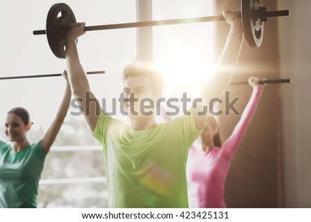 fitness, sport, training, gym and lifestyle concept - group of people exercising with barbell in gym - stock photo