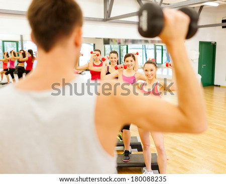 fitness, sport, training, gym and lifestyle concept - group of smiling female with dumbbells and aerobic step an trainer infront - stock photo