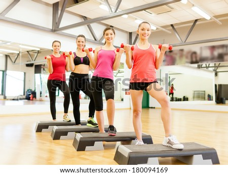 fitness, sport, training, gym and lifestyle concept - group of smiling female with dumbbells and aerobic step - stock photo