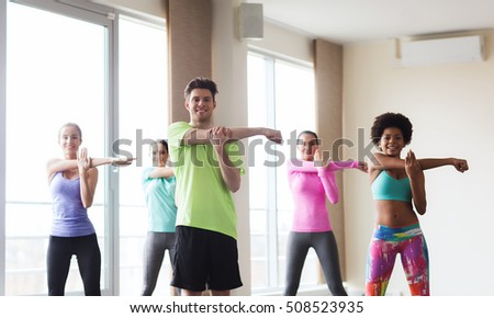 fitness, sport, training, gym and lifestyle concept - group of smiling people stretching in gym