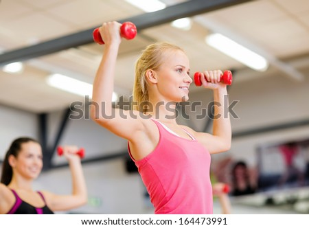 fitness, sport, training, gym and lifestyle concept - group of smiling people working out with dumbbells in the gym - stock photo