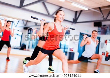 fitness, sport, training, gym and lifestyle concept - group of smiling people working out with barbells in the gym - stock photo