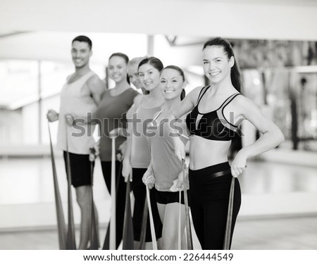 fitness, sport, training, gym and lifestyle concept - group of smiling people working out with rubber bands in the gym - stock photo