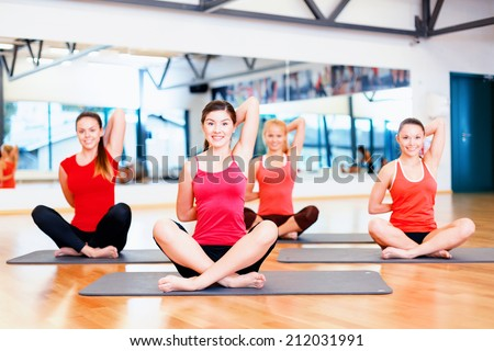 fitness, sport, training, gym and lifestyle concept - group of smiling women stretching on mats in the gym - stock photo
