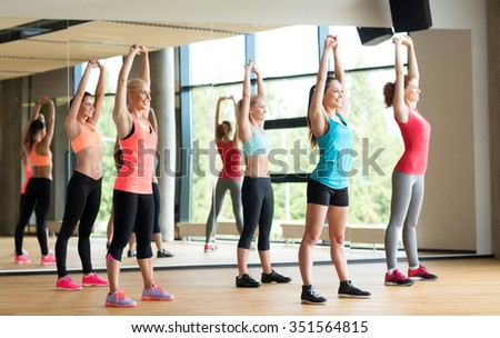 fitness, sport, training, gym and lifestyle concept - group of women working out in gym - stock photo