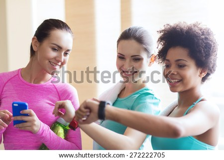 fitness, sport, training, gym and lifestyle concept - happy women showing time on wrist watch in gym - stock photo