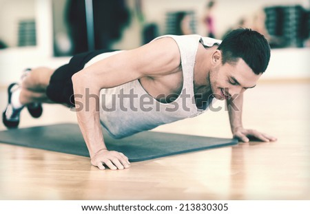 fitness, sport, training, gym and lifestyle concept - smiling man doing push-ups in the gym - stock photo