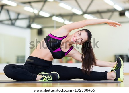 fitness, sport, training, gym and lifestyle concept - smiling teenage girl stretching on mat in the gym - stock photo