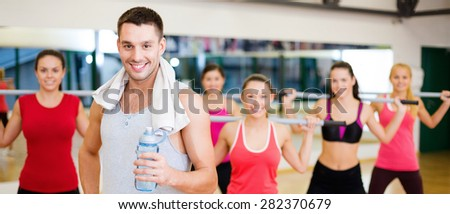fitness, sport, training, gym and lifestyle concept - smiling trainer in front of group of people working out with barbells in the gym - stock photo
