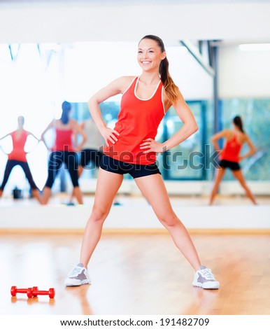 fitness, sport, training, gym and lifestyle concept - smiling trainer working out in the gym - stock photo