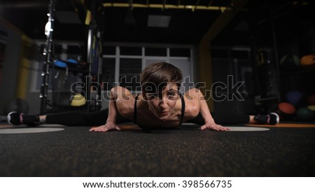 fitness, sport, training, gym and lifestyle concept - stretching young woman with earphones in the gym. - stock photo
