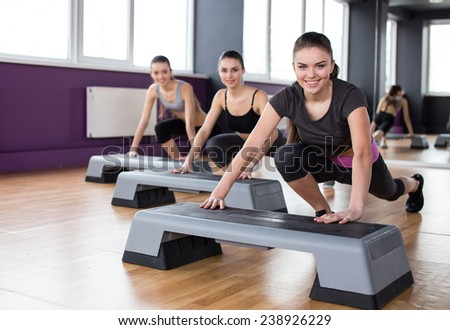 Fitness, sport, training, gym and lifestyle concept. Three young women are working out with steppers in gym. - stock photo
