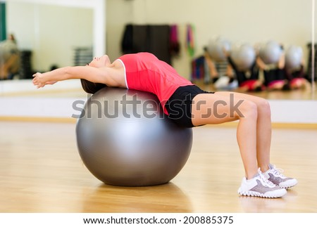 fitness, sport, training, gym and lifestyle concept - young woman doing exercise on fitness ball - stock photo