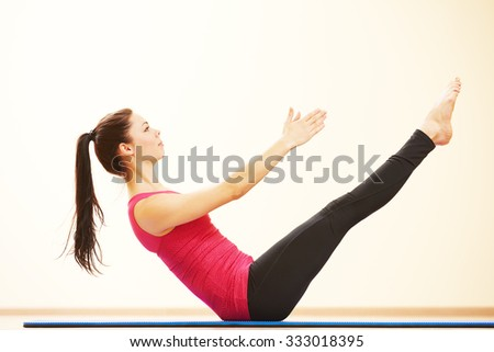 fitness, sport, training, gym and wellness. Woman doing stretching excercises on the fitness mat in gym - stock photo