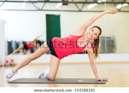 fitness, sport, training, gym, technology and lifestyle concept - smiling teenage girl with smartphone and earphones in gym - stock photo