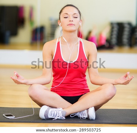 fitness, sport, training, gym, technology and lifestyle concept - smiling teenage girl with smartphone and earphones meditating in gym