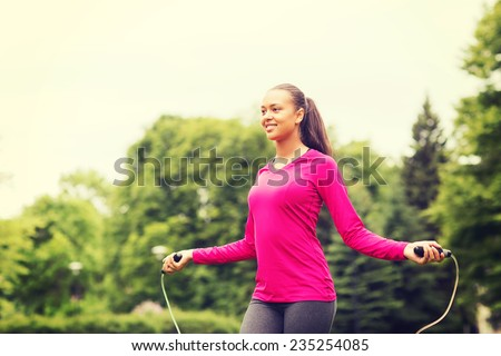 fitness, sport, training, park and lifestyle concept - smiling african american woman exercising with jump-rope outdoors - stock photo