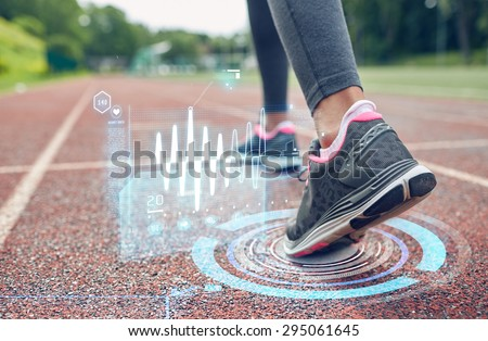 fitness, sport, training, people and healthy lifestyle concept - close up of woman feet running on track with futuristic holograms from back - stock photo
