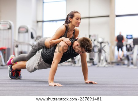 fitness, sport, training, teamwork and lifestyle concept - smiling couple doing push-ups in the gym - stock photo