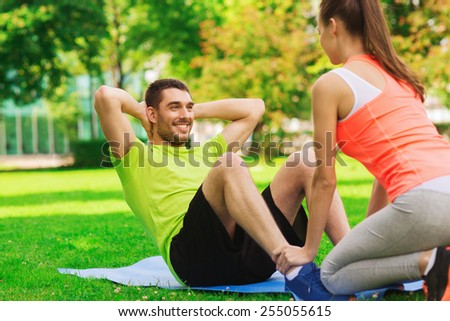 fitness, sport, training, teamwork and lifestyle concept - smiling man with personal trainer doing exercises on mat outdoors - stock photo