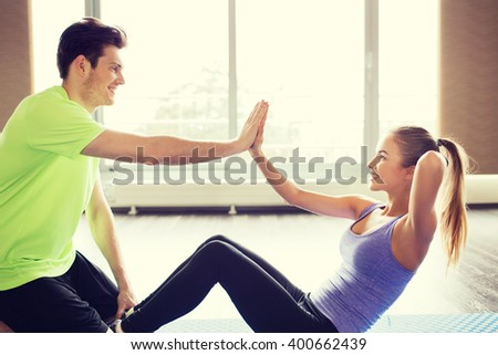 fitness, sport, training, teamwork and people concept - happy woman with personal trainer doing sit ups and high five gesture in gym - stock photo