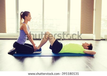fitness, sport, training, teamwork and people concept - woman with personal trainer doing sit ups in gym - stock photo