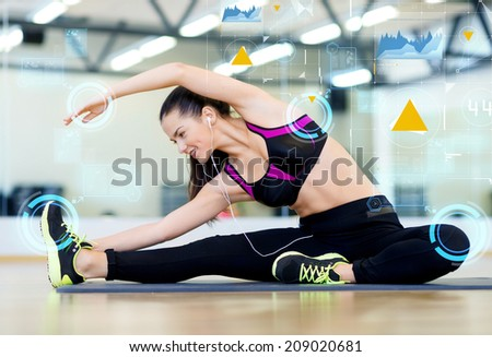 fitness, sport, training, technology and lifestyle concept - smiling young woman stretching on mat in gym - stock photo