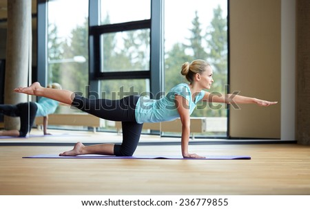 fitness, sport, training, yoga and people concept - smiling woman doing exercise in gym - stock photo