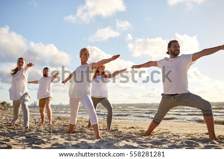 fitness, sport, yoga and healthy lifestyle concept - group of people making warrior pose on beach